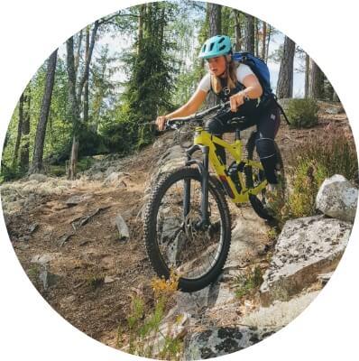 Jente sykler på sti gjennom skogen