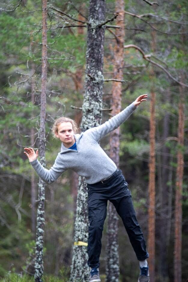 Person som balanserer på line gjennom skogen