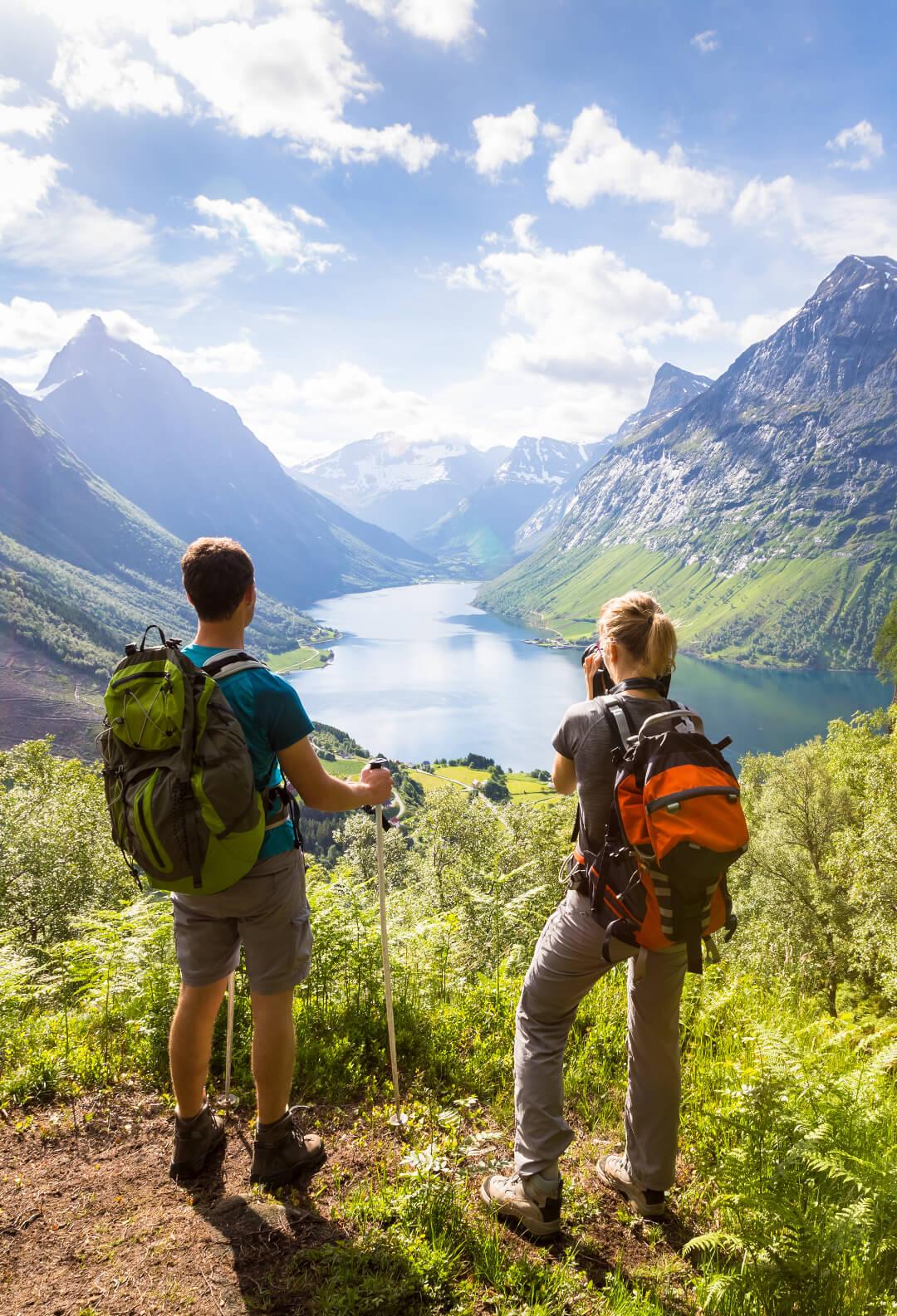 To turgårere tar bilde av fjelltoppene og en innsjø