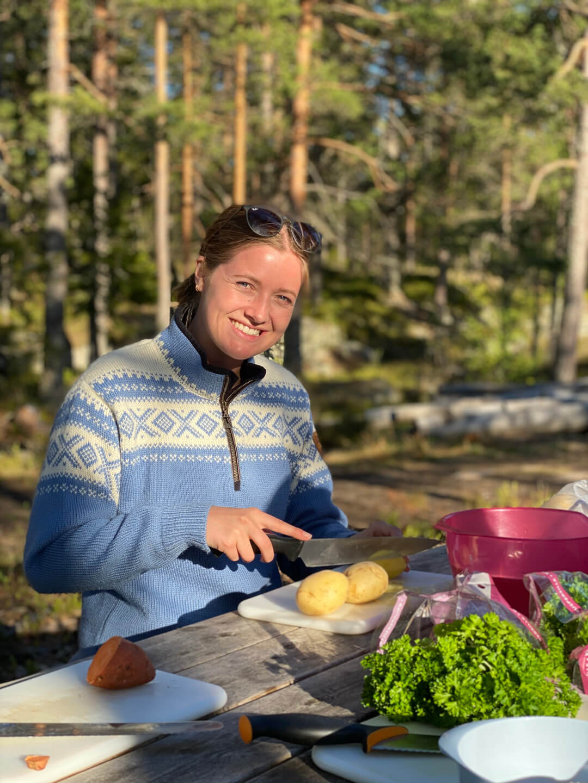 Kvinne som lager mat i naturen.