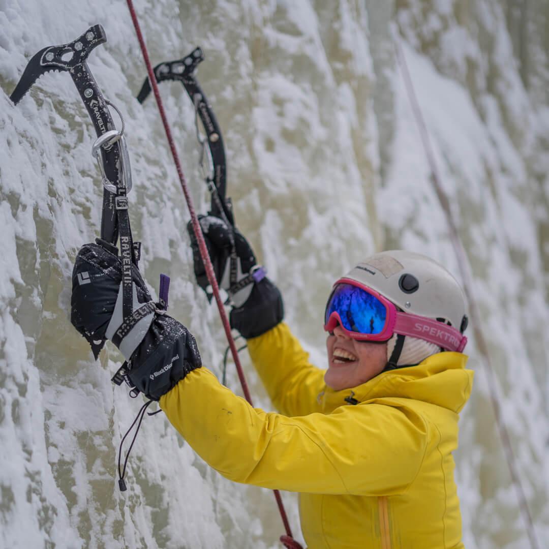 Elev i gul jakke som klatrer på isen og smiler