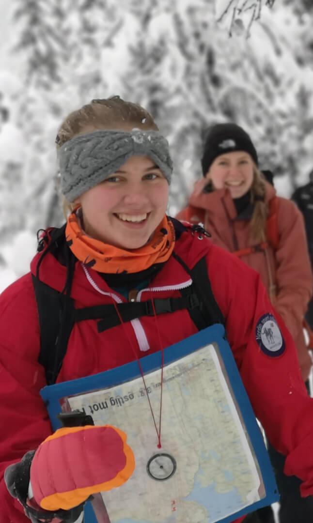 jente med kart og kompass smiler