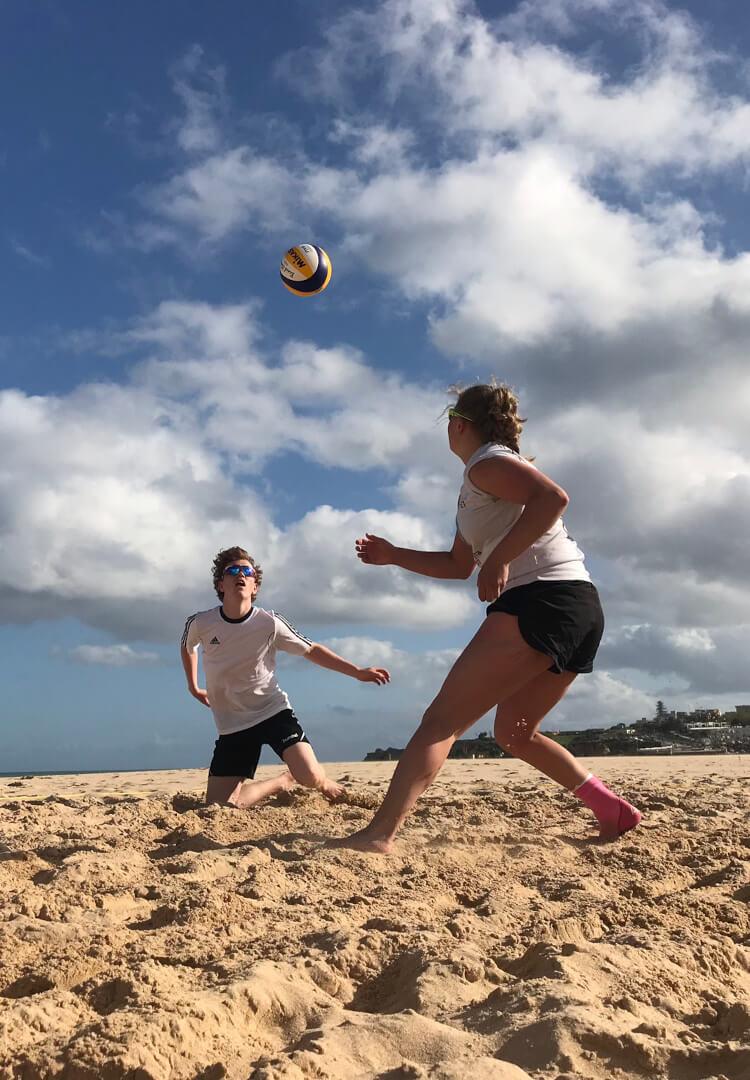 To elever spiller volleyball i sanden på stranden