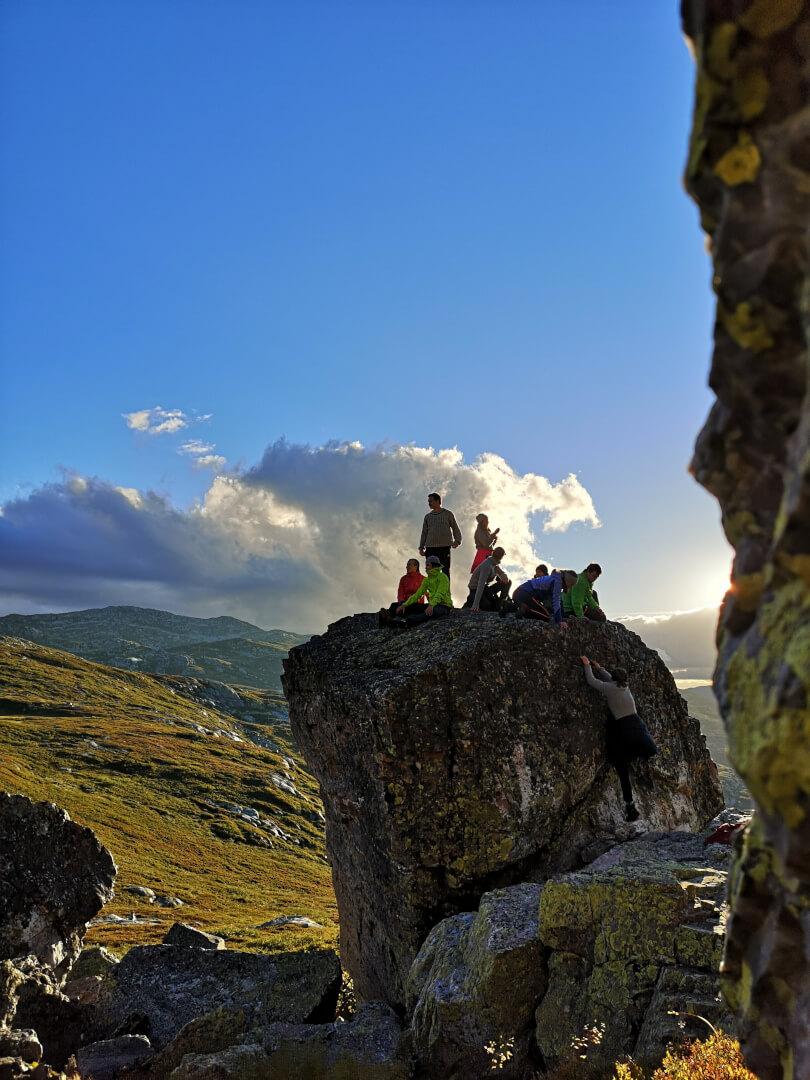 Mennesker på toppen av en stor stein i norsk natur