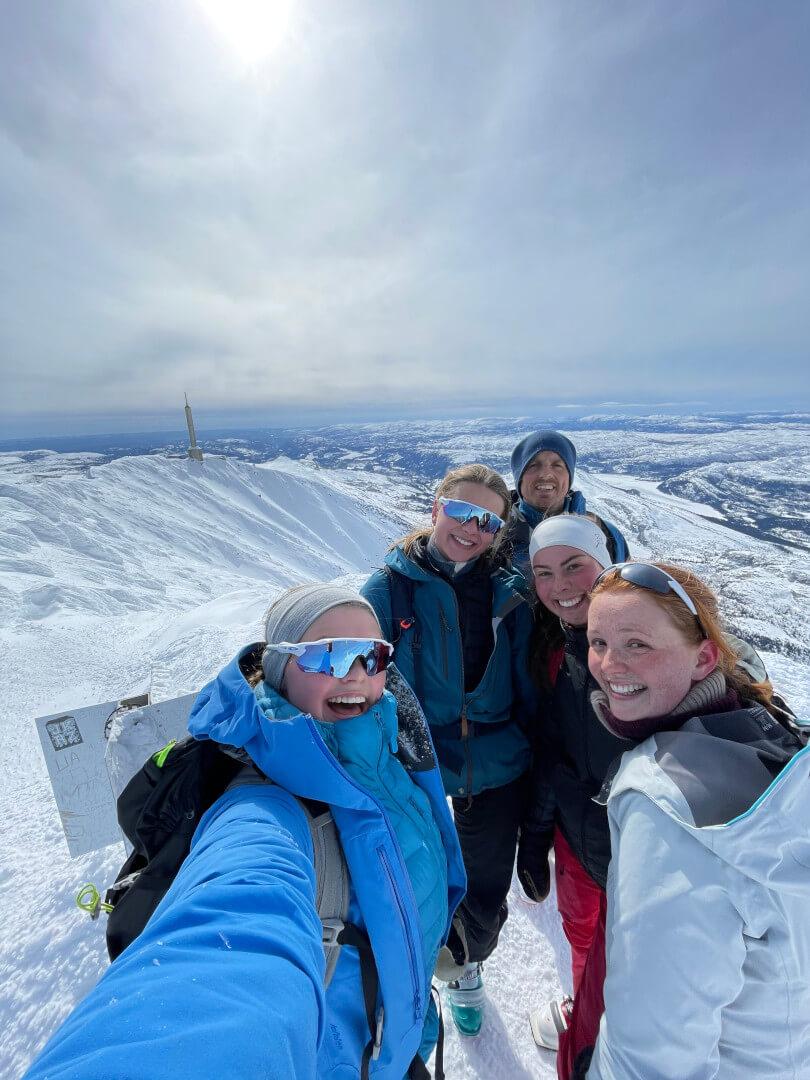 Fem personer tar selfie i snøen på toppen av et fjell
