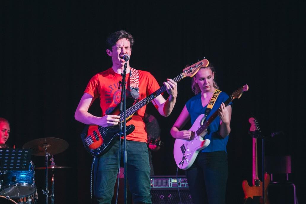 To elever som spiller gitar og synger på scene