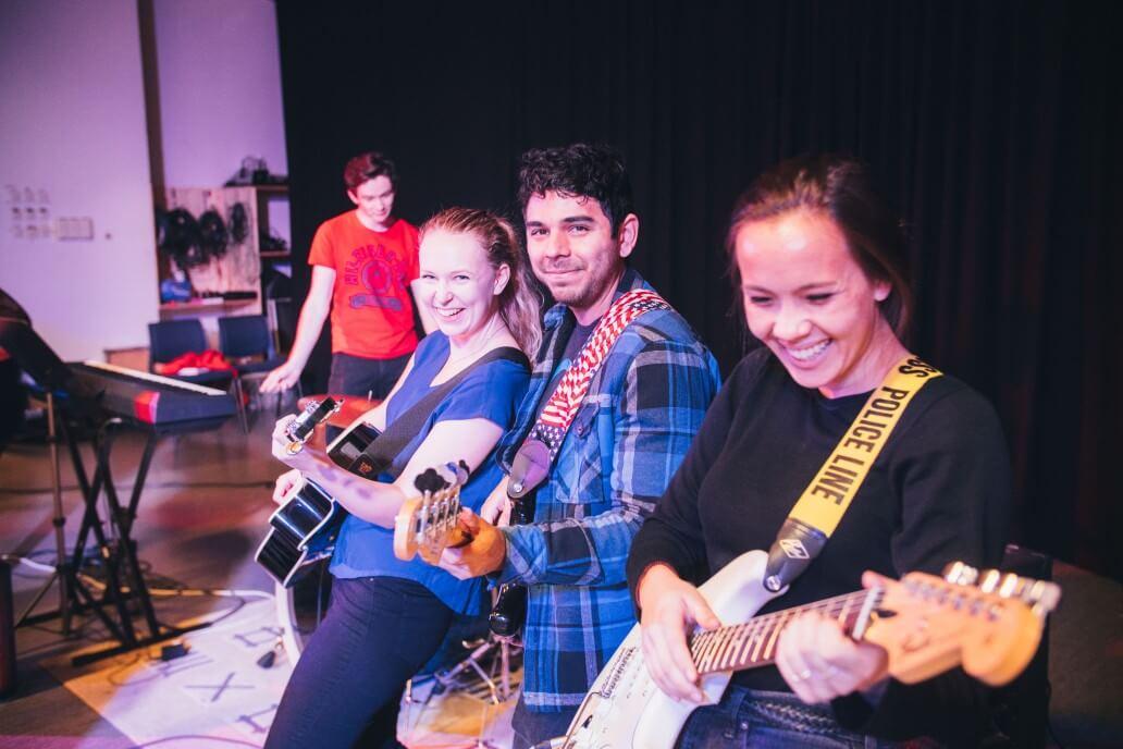 Tre elever som spiller gitar og ler