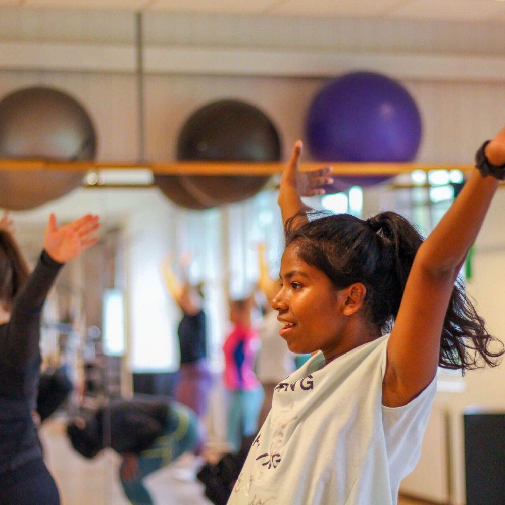 Elever med armene i været som øver på dans
