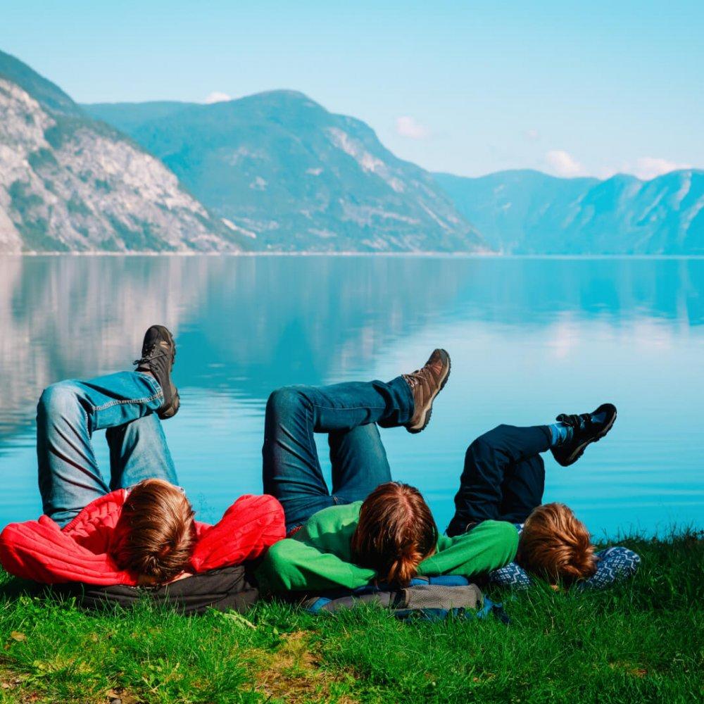 Tre mennesker hvilker med beina opp ved en innsjø