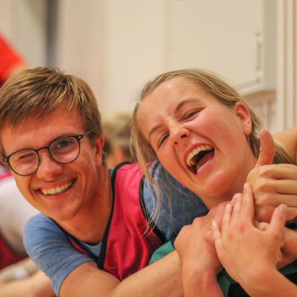 To elever som holder rundt hverandre og ler